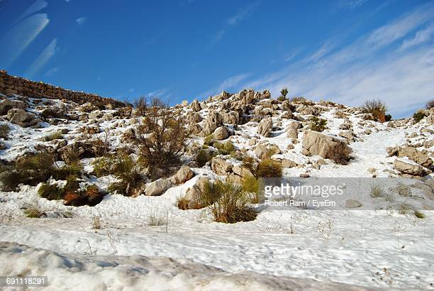 Snow Covered Landscape Against Blue Sky