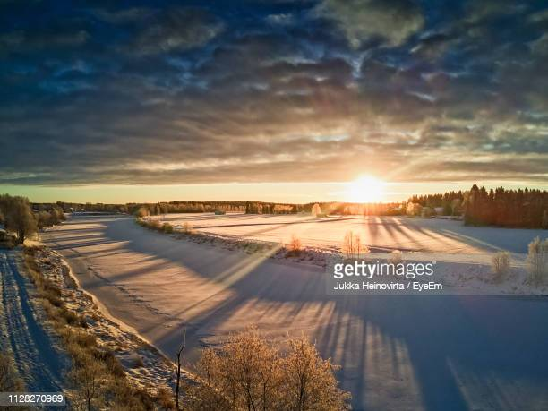snow covered landscape against sky during sunset - heinovirta stock photos and pictures
