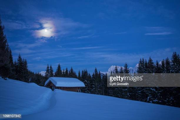 snow covered log cabin and wetterstein mountain range at night - mittenwald stock pictures, royalty-free photos & images