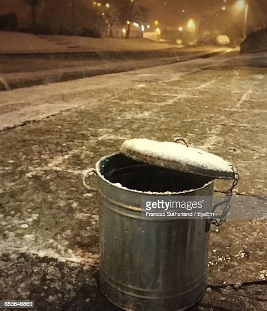 Snow Covered Metallic Garbage Can On Street At Night