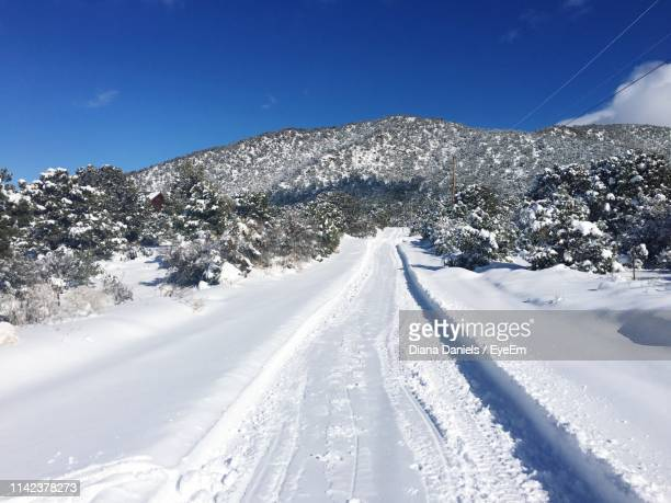 snow covered mountain against blue sky - diana daniels stock-fotos und bilder