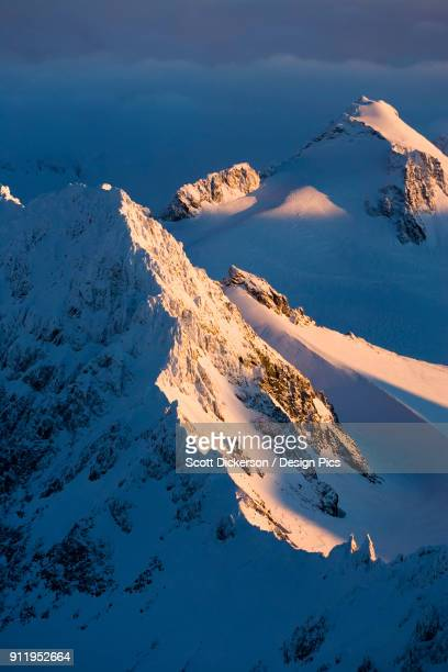 a snow covered mountain covered by shadows and sunlight, kachemak bay state park - kachemak bay stock pictures, royalty-free photos & images