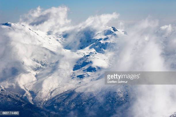 Snow covered mountain range in the clouds