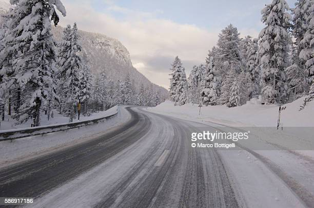 snow covered mountain road in winter. switzerland, europe. - mountain road stock pictures, royalty-free photos & images