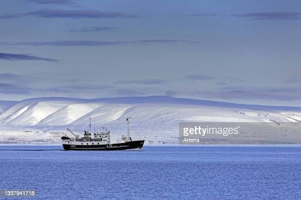 Snow covered mountains and boat with tourists during fjord-cruise in Billefjorden in autumn, Svalbard. Spitsbergen, Norway.