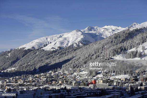 Snow covered mountains are seen standing beyond commercial buildings and residential apartments from a guests' bedroom balcony at the...