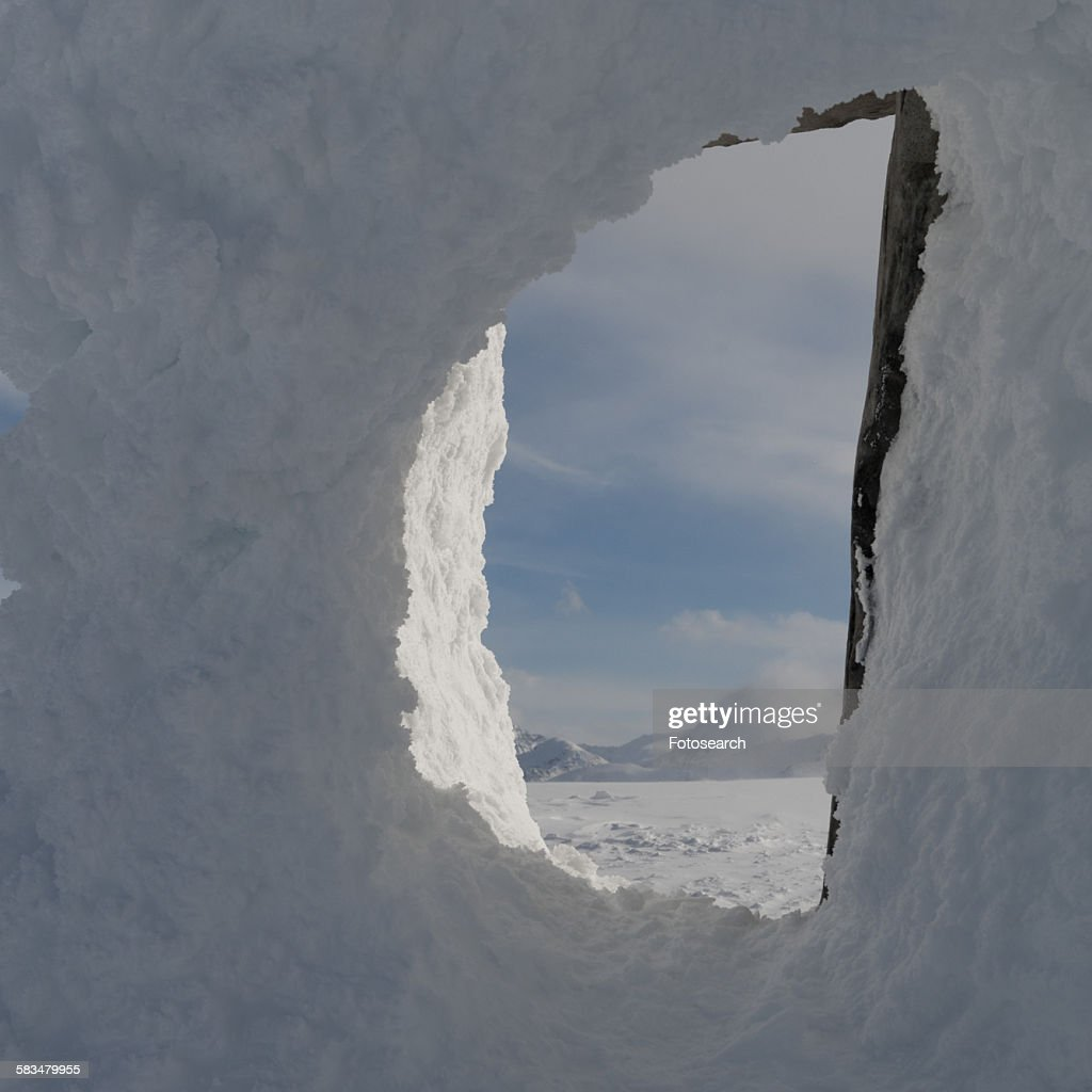Snow covered mountains viewed through a snow covered inuksuk : Stock Photo