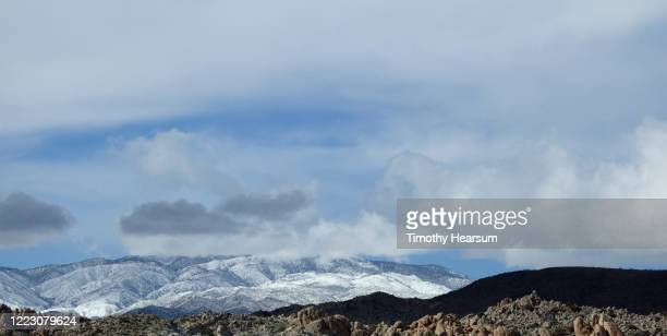 snow covered mountains with a sliver of rocky hills in foreground; blue sky and clouds beyond near joshua tree national park - timothy hearsum stockfoto's en -beelden