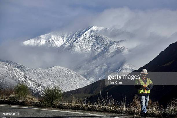 JANUARY 07 2016 Snow covered Mt Baldy shines in morning light behind LA county surveyors working on Mt Baldy Road