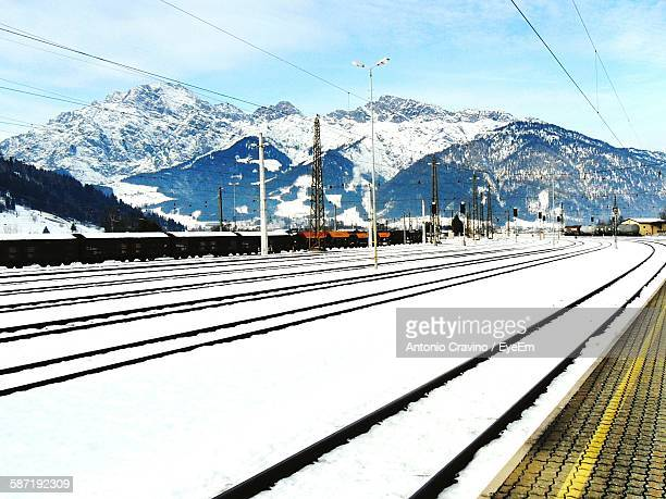 snow covered railroad tracks against mountains during winter at saalfelden - saalfelden stock pictures, royalty-free photos & images