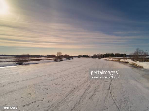 snow covered road against sky during sunset - heinovirta stock photos and pictures