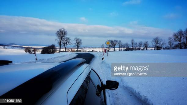 snow covered road against sky - andreas solar stock pictures, royalty-free photos & images