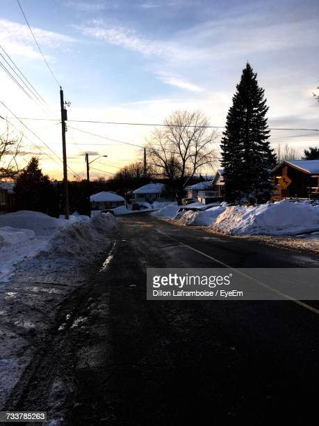 snow covered road against sky - sudbury canada stock photos and pictures