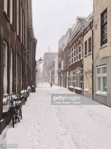 snow covered road amidst buildings in city - bortes stock pictures, royalty-free photos & images