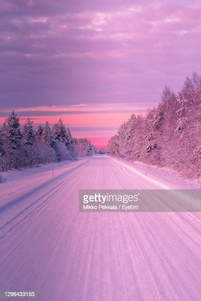 snow covered road amidst trees against sky at sunset - finland stock pictures, royalty-free photos & images