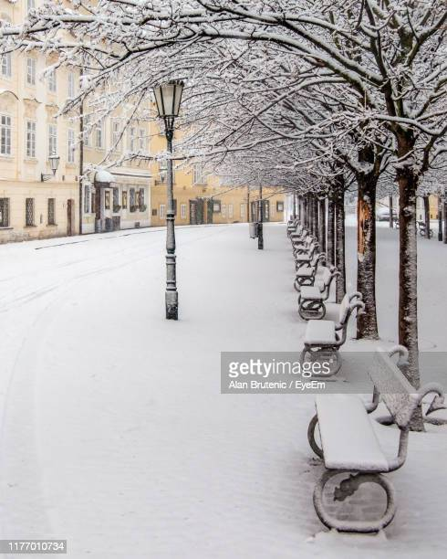 snow covered road by buildings in city - czech republic stock pictures, royalty-free photos & images