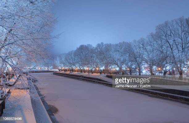 snow covered road by trees against sky in city - トゥルク ストックフォトと画像