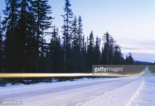 Snow covered road with lights streaks from vehicle (long exposure)