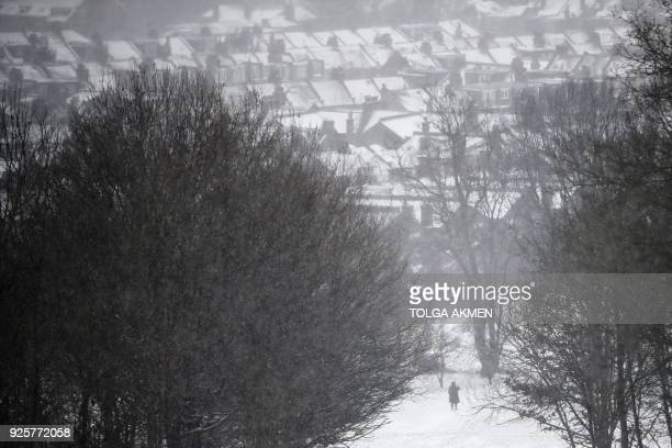 Snow covered roofs are seen in the distance from Alexandra Palace north London on March 1 2018 Fresh heavy snowfalls and icy blizzards were expected...