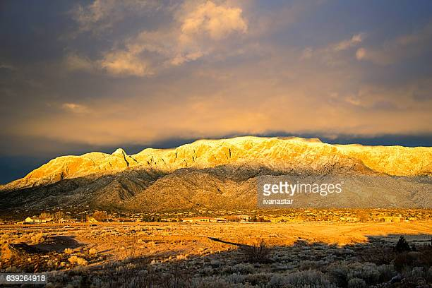 snow covered sandia mountains at sunset - sandia mountains stock pictures, royalty-free photos & images