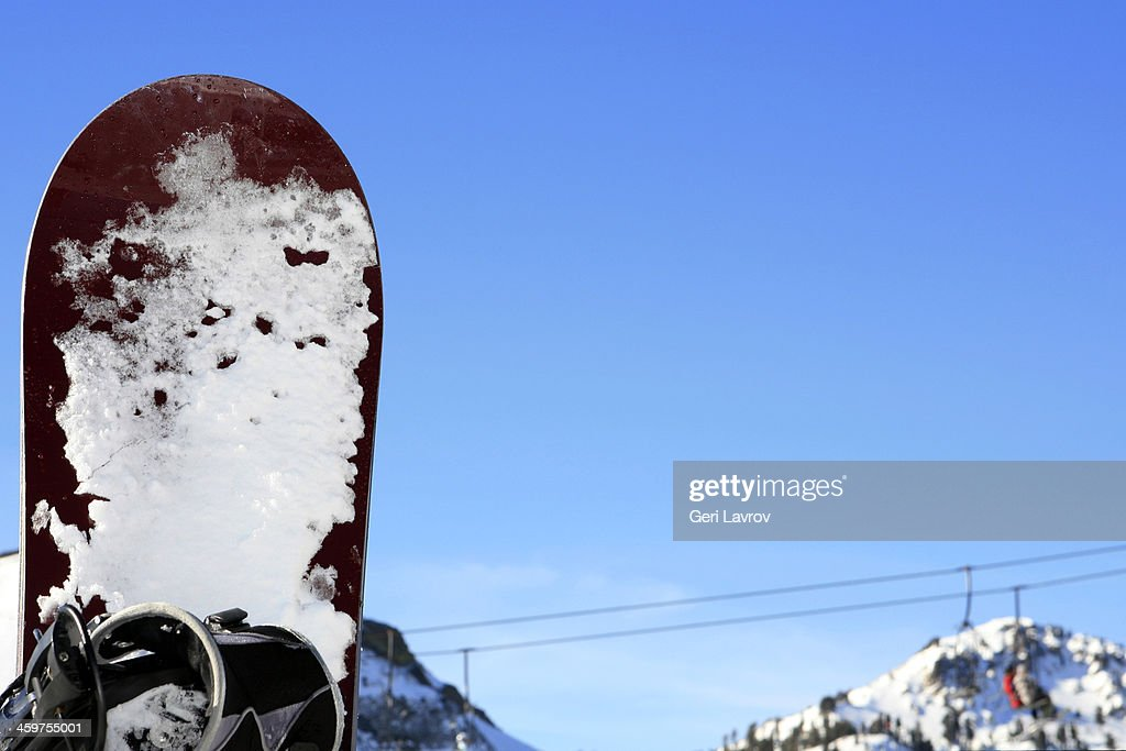 Snow covered snowboard by a chair lift : ストックフォト