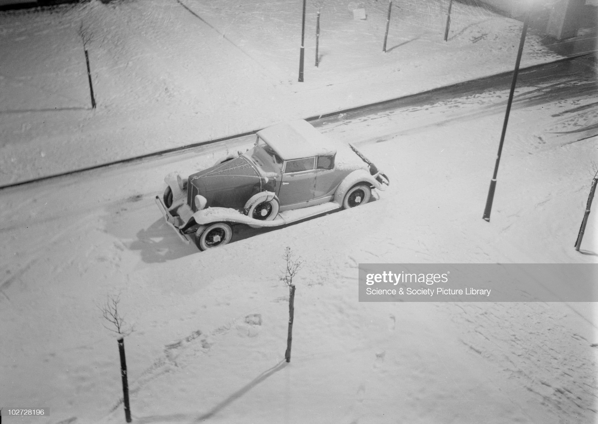 Snow covered stationary car on a street. Photograph taken by Zoltan Glass, c.1930. : News Photo