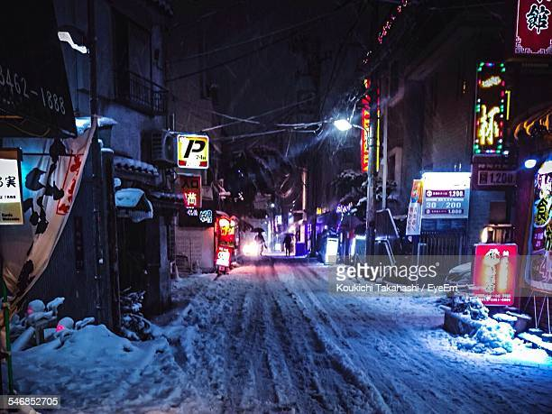 Snow Covered Street Amidst Buildings At Night