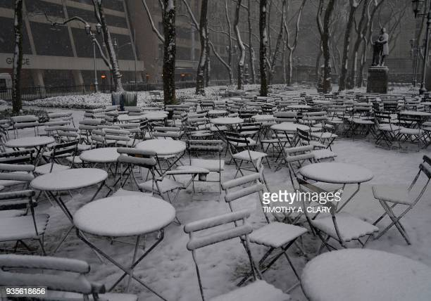Snow covered tables in Bryant Park in New York March 21 2018 as the fourth nor'easter in a month hits the tristate area on the first full day of...