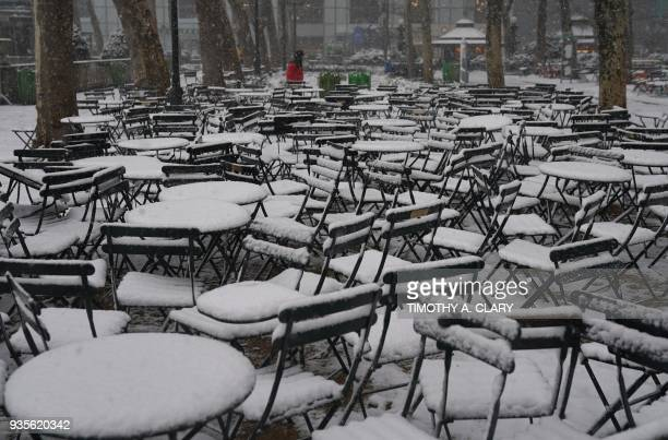 TOPSHOT Snow covered tables in Bryant Park in New York March 21 2018 as the fourth nor'easter in a month hits the tristate area on the first full day...