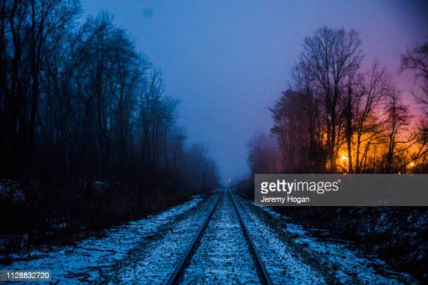snow covered train tracks at dusk in winter - bloomington indiana stock photos and pictures