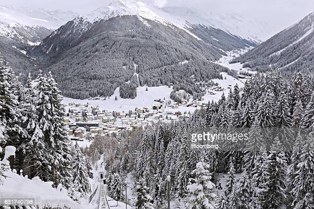 Snow covered trees and mountains surround buildings in Davos Switzerland on Sunday Jan 15 2017 World leaders influential executives bankers and...