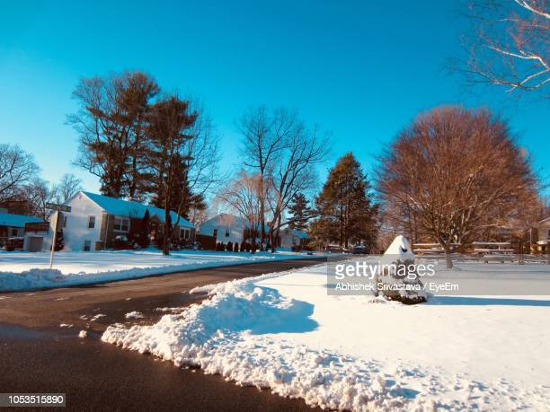 Snow Covered Trees By House Against Clear Blue Sky