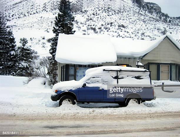 Snow covered truck and house roof top with icicles after snowstorm in the mountains