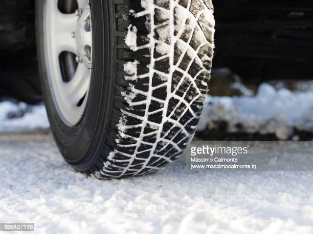 snow covered tyre on snowy road - road salt stock pictures, royalty-free photos & images