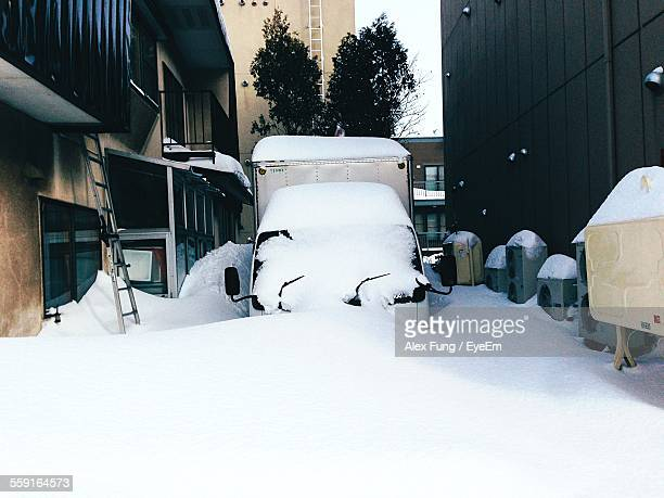 Snow Covered Vehicle On Tree Amidst Buildings