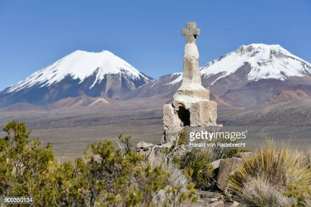 Snow covered volcanoes Pomerape and Parinacota with small chapel, Sajama National Park, Bolivian Bolivia border Chile