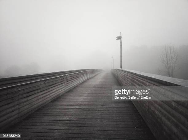 Snow Covered Walkway Against Sky During Foggy Weather