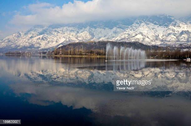 Snow covered Zabarwan mountains are reflected on the waters of Dal lake on January 21 2012 in Srinagar the summer capital of Indian Administered...