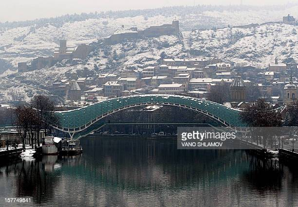 Snow covers a bridge crossing the Kura river in Tbilisi and the surrounding building on February 20 2011 AFP PHOTO / VANO SHLAMOV