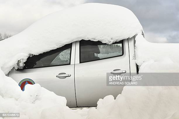 Snow covers a car of the Italian Civil Protection parked at a nearby sports ground in Montereale after a 57magnitude earthquake struck the region on...
