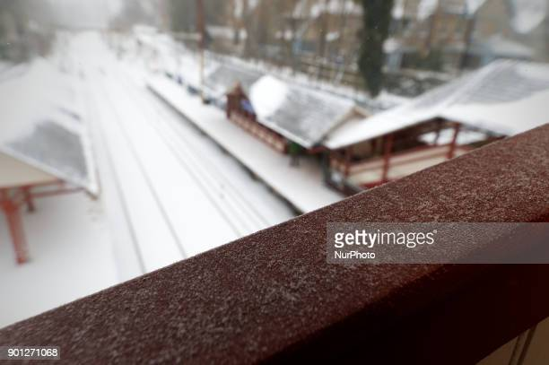 Snow covers a pedestrian bridge railing as trains are delayed when the region feels the impact of the 'Bomb Cyclone' winter storm Grayson on January...