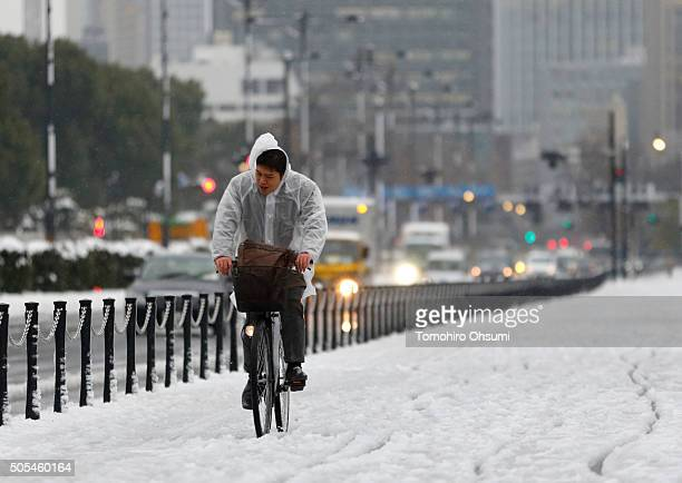Snow covers a road as a commuter rides on a bicycle near the Imperial Palace on January 18 2016 in Tokyo Japan The first heavy snowfall of the season...
