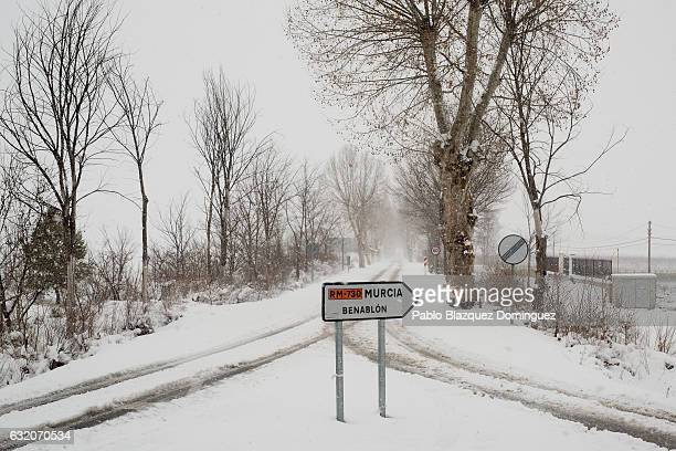 Snow covers a street as a traffic sign reads 'Murcia Benablon' on January 19 2017 in Barranda in Murcia province Spain The cold weather has brought...