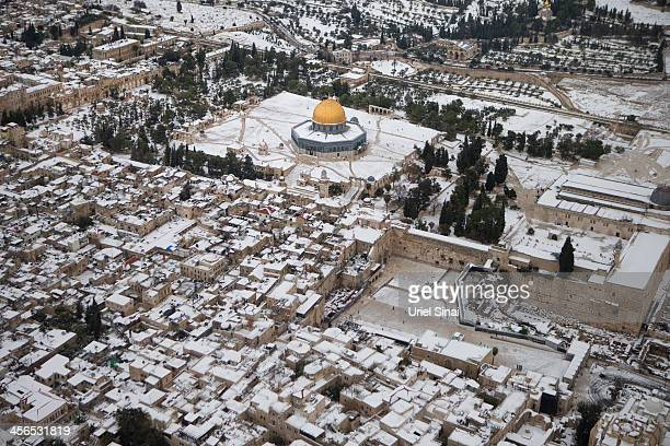 Snow covers the Dome of the Rock at the AlAqsa mosque compound as well as the Western Wall on December 14 2013 in Jerusalem's old city Israel Heavy...