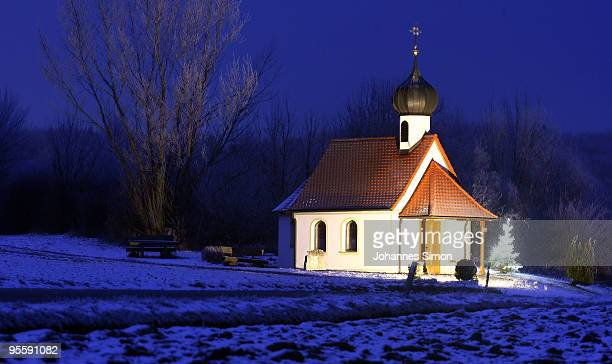 Snow covers the little chapel of Auing during dusk on January 5 2010 near Steinebach am Woerthsee Germany Currently freezing temperature around minus...
