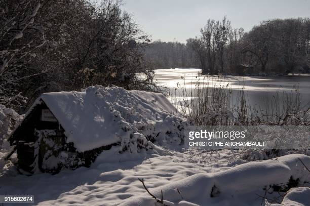 Snow covers the roof of a shelter by a partiallyfrozen lake near Orleans some 120 km south of Paris on February 8 2018 / AFP PHOTO / CHRISTOPHE...