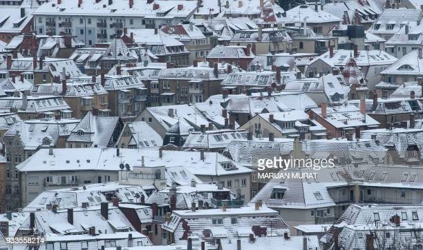 TOPSHOT Snow covers the roofs of houses in Stuttgart southern Germany on March 18 2018 / AFP PHOTO / dpa / Marijan Murat / Germany OUT