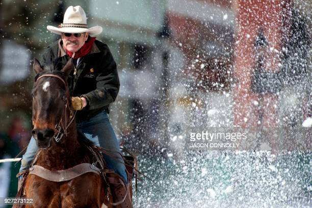 Snow explodes around Jeff Dahl of Durango Colorado as he races down Harrison Avenue on his horse Cash while pulling his son and skier Jason Dahl...
