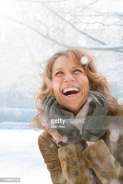 Snow falling on smiling woman