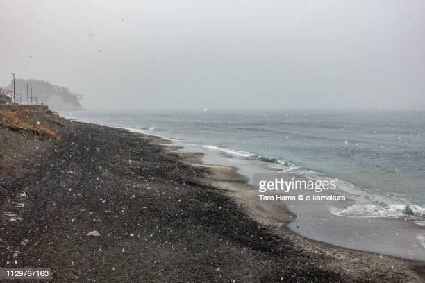 Snow falling on the beach in Kamakura in Japan